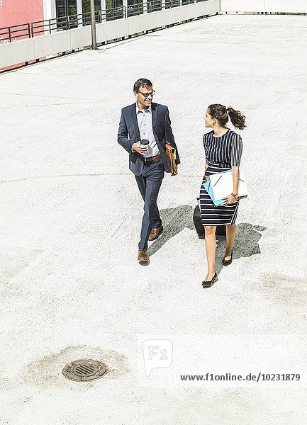 Erwachsener Geschäftsmann und junge Frau mit Laufkatze im Hof