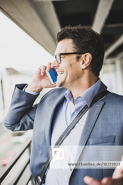 Lächelnder Geschäftsmann telefoniert mit Smartphone
