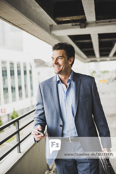 Portrait of happy businessman with briefcase and smartphone
