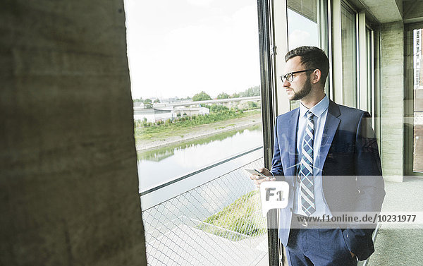 Young businessman with cell phone looking out of window