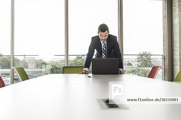 Junger Geschäftsmann im Konferenzraum mit Blick auf den Laptop