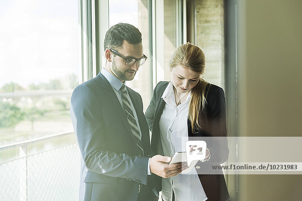Young businessman and businesswoman at the window looking on digital tablet