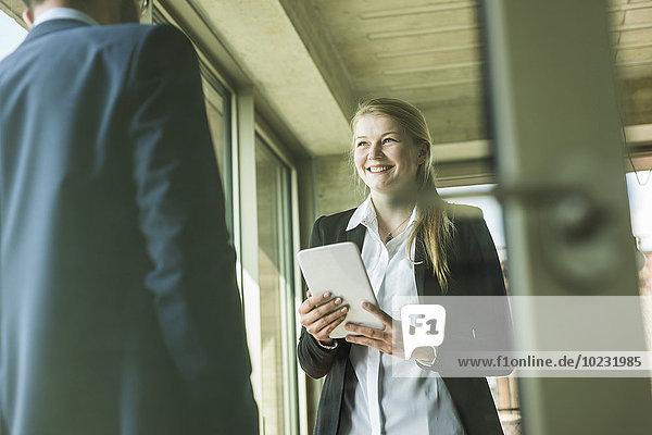 Lächelnde junge Geschäftsfrau mit digitalem Tablett beim Anblick des Geschäftsmannes