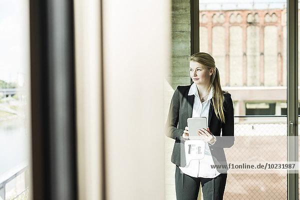 Junge Geschäftsfrau am Fenster mit digitalem Tablett