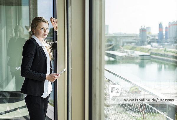 Junge Geschäftsfrau mit digitalem Tablett aus dem Fenster schauend