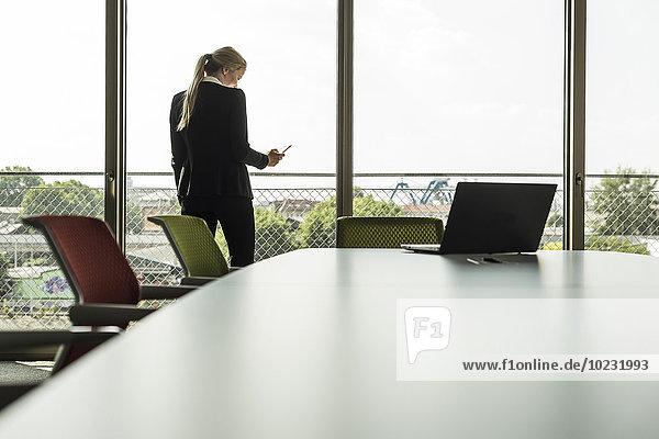Junge Geschäftsfrau im Konferenzraum mit Blick aufs Handy