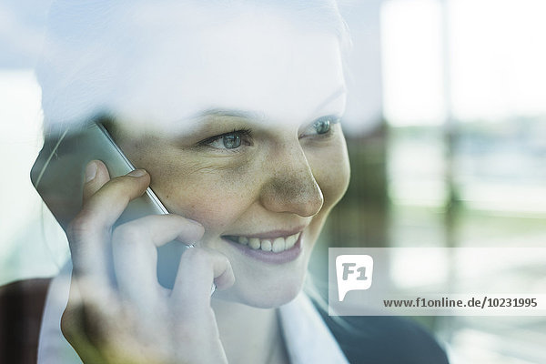 Lächelnde junge Geschäftsfrau hinter der Fensterscheibe auf dem Handy