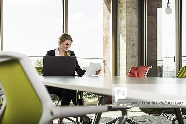 Junge Geschäftsfrau im Konferenzraum beim Betrachten von Dokumenten