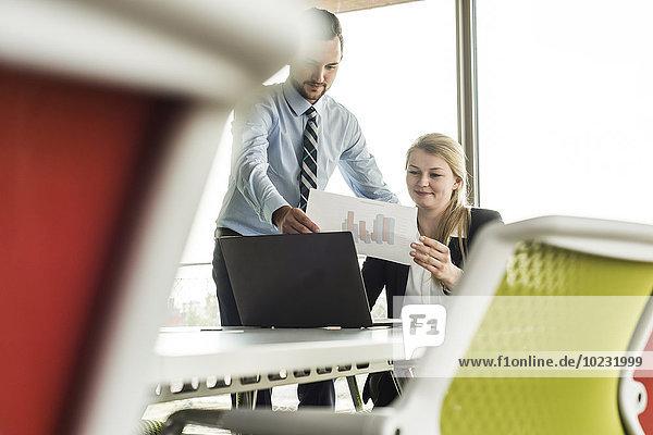 Jungunternehmerin im Konferenzraum mit Laptop und Diagramm