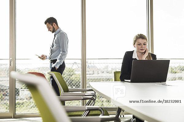 Geschäftsmann und junge Geschäftsfrau im Konferenzraum mit Laptop