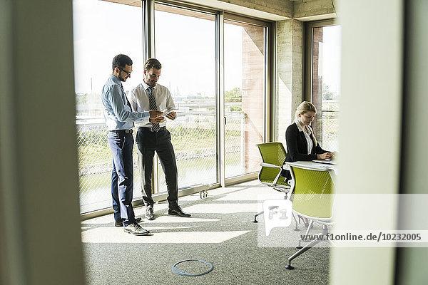 Zwei Geschäftsleute mit digitalem Tablett und Geschäftsfrau im Konferenzraum