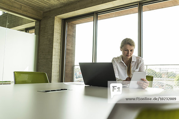Young businesswoman in conference room with laptop and digital tablet