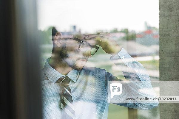 Nachdenklicher junger Geschäftsmann hinter der Fensterscheibe