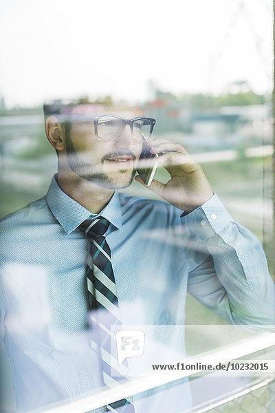 Junger Geschäftsmann am Handy hinter der Fensterscheibe