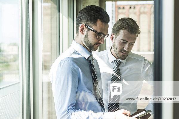 Zwei junge Geschäftsleute mit Smartphone am Fenster