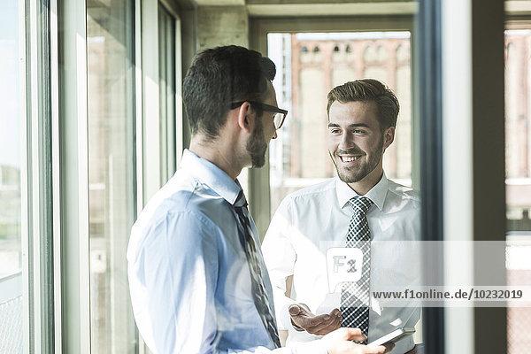 Zwei glückliche junge Geschäftsleute mit Smartphone am Fenster