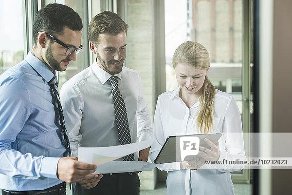 Drei junge Geschäftsleute  die sich Dokumente und digitales Tablett ansehen