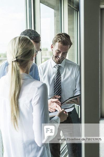 Drei junge Geschäftsleute,  die sich Dokumente und digitales Tablett ansehen