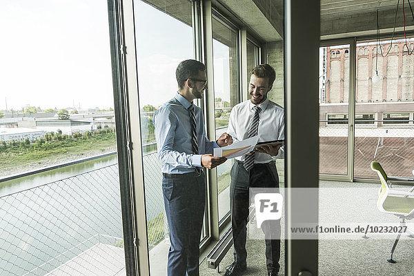 Zwei junge Geschäftsleute schauen sich Dokumente und digitales Tablett am Fenster an.