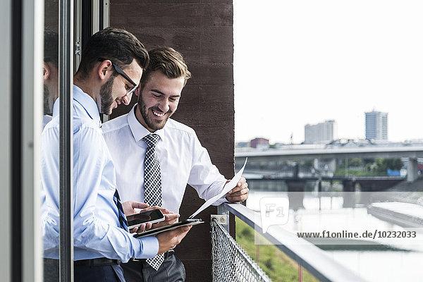 Zwei junge Geschäftsleute mit Dokumenten  Smartphone und digitalem Tablett auf dem Balkon