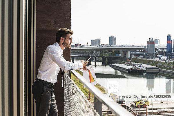 Junger Geschäftsmann auf dem Balkon stehend mit Blick auf die Aussicht