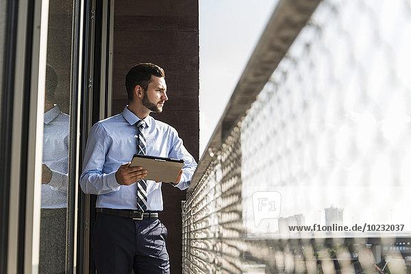 Jungunternehmer auf dem Balkon stehend mit digitalem Tablett