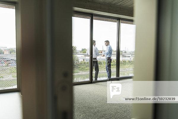 Zwei junge Geschäftsleute,  die auf dem Balkon stehen und reden.