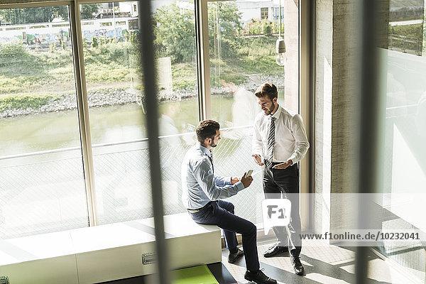 Zwei junge Geschäftsleute mit Smartphones im Gespräch