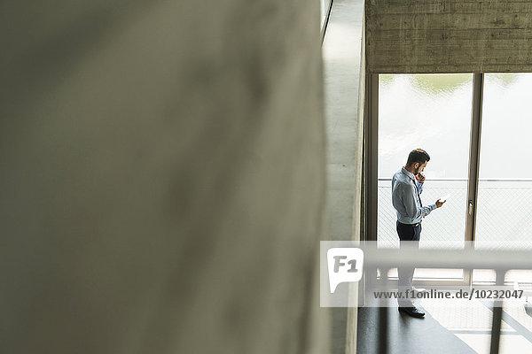 Junger Geschäftsmann schaut auf das Handy am Fenster