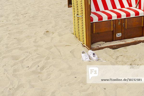 Paar Turnschuhe und Strandkorb mit Kapuze am Strand