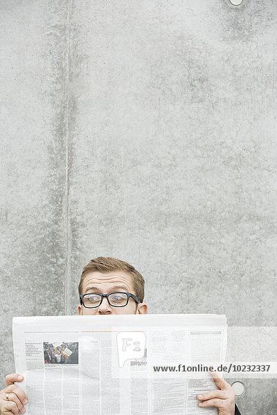 Überraschter Mann liest Zeitung an der Betonwand