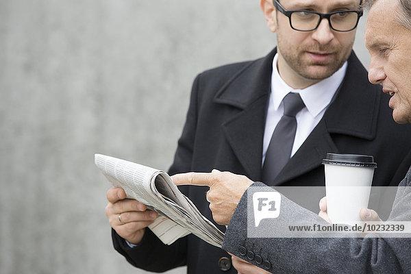 Zwei Geschäftsleute mit Kaffee zum Mitnehmen und Zeitung