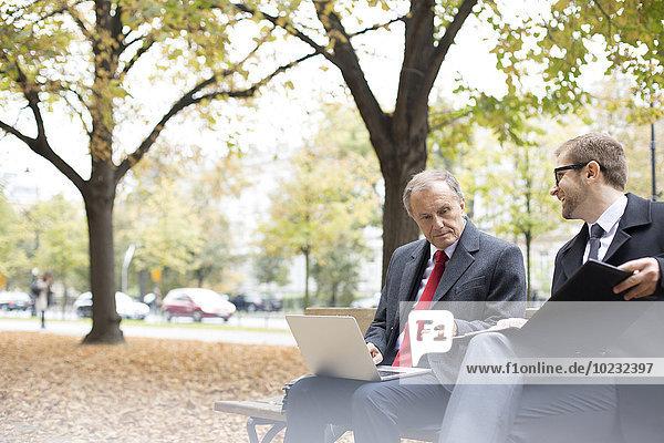 Zwei Geschäftsleute mit Laptop und Unterlagen auf der Parkbank