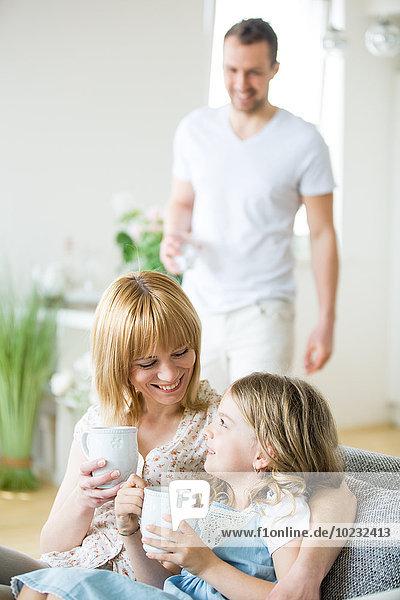 Mutter und Tochter sitzen auf der Couch und trinken Tee  Vater im Hintergrund
