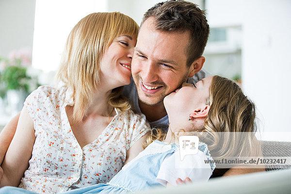 Glückliche Familie auf der Couch sitzend  Mutter und Tochter küssen Vater