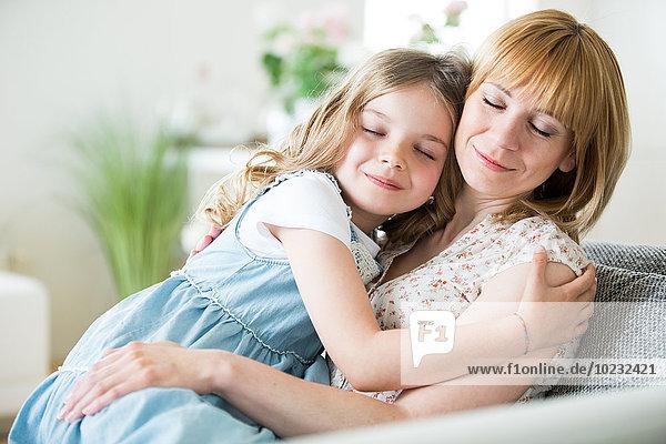Mutter und Tochter auf der Couch sitzend  kuschelnd
