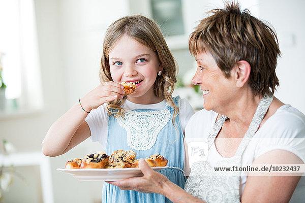 Großmutter und Enkelin in der Küche mit Gebäckteller