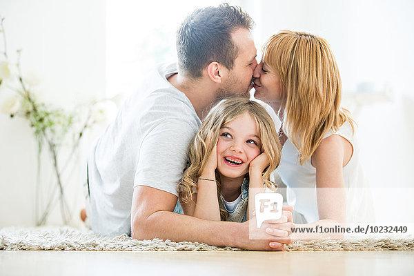 Glückliches Mädchen auf dem Boden liegend  Eltern küssend