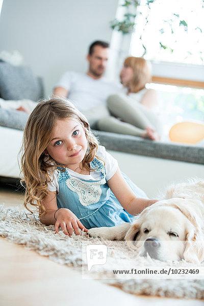 Kleines Mädchen kuschelt mit ihrem Hund  auf dem Boden liegend  Eltern im Hintergrund