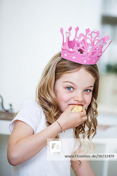 Mädchen mit rosa Krone isst Kuchen Mädchen mit rosa Krone isst Kuchen