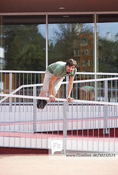 Junger Mann springt über Geländer