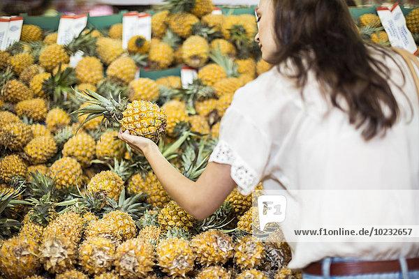 Frau kontrolliert Ananas am Obststand