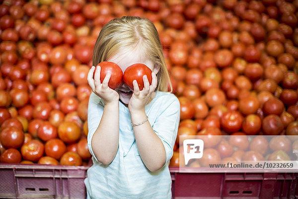 Kleines Mädchen vor dem Tomatenstand  das die Augen mit Tomaten bedeckt.