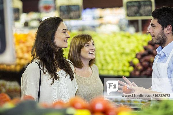 Verkäuferin hilft Kunden bei der Auswahl der Früchte