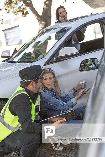 Frau im Gespräch mit Polizist am Unfallort