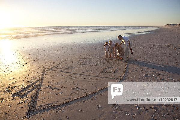 Familie am Strand mit gezeichnetem Haus im Sand