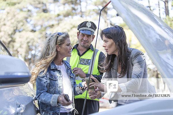 Zwei Frauen und Polizistinnen diskutieren am Unfallort