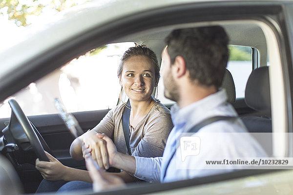 Teenager Mädchen in einem Auto schüttelt Handflächen mit Fahrinspektor