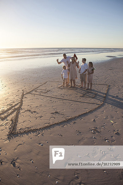 Family on beach with drawn house in the sand