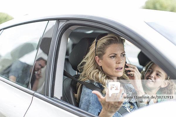 Frustrierte Frau im Auto mit Kind im Stau